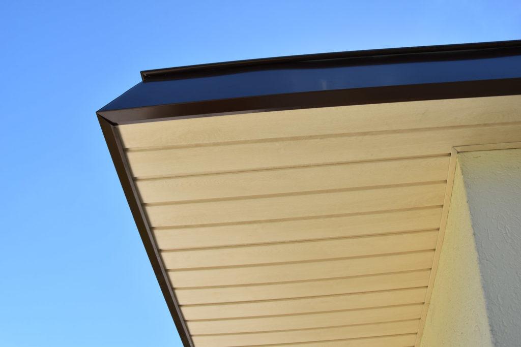 habillage des dessous de toit de couleur chêne clair. Recouvrement du bandeau marron et finition par une main courante.