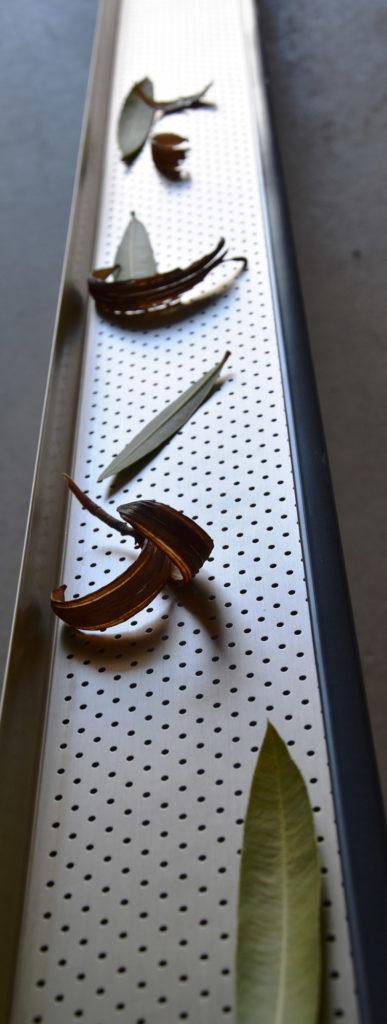 Grille pares-feuilles installée dans une gouttière pour montrer qu'elle permet de retenir les feuilles sans empêcher l'évacuation de l'eau